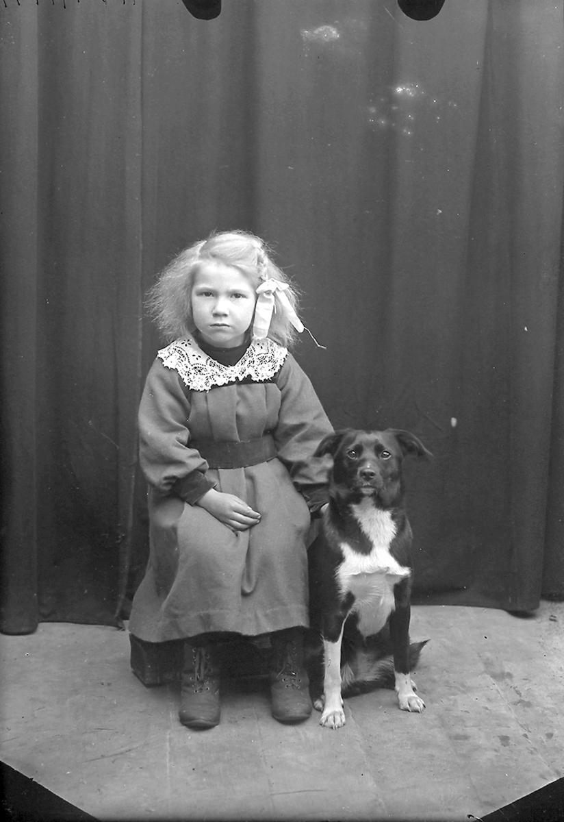 Portrett. Pike med hund av type bastard. Piken og hunden sitter, hunden sitter ved siden av piken. Piken har på seg mørk kjole med hvit krage og hårsløyfe på den ene siden.Bildet er tatt på Reine i Lofoten.
