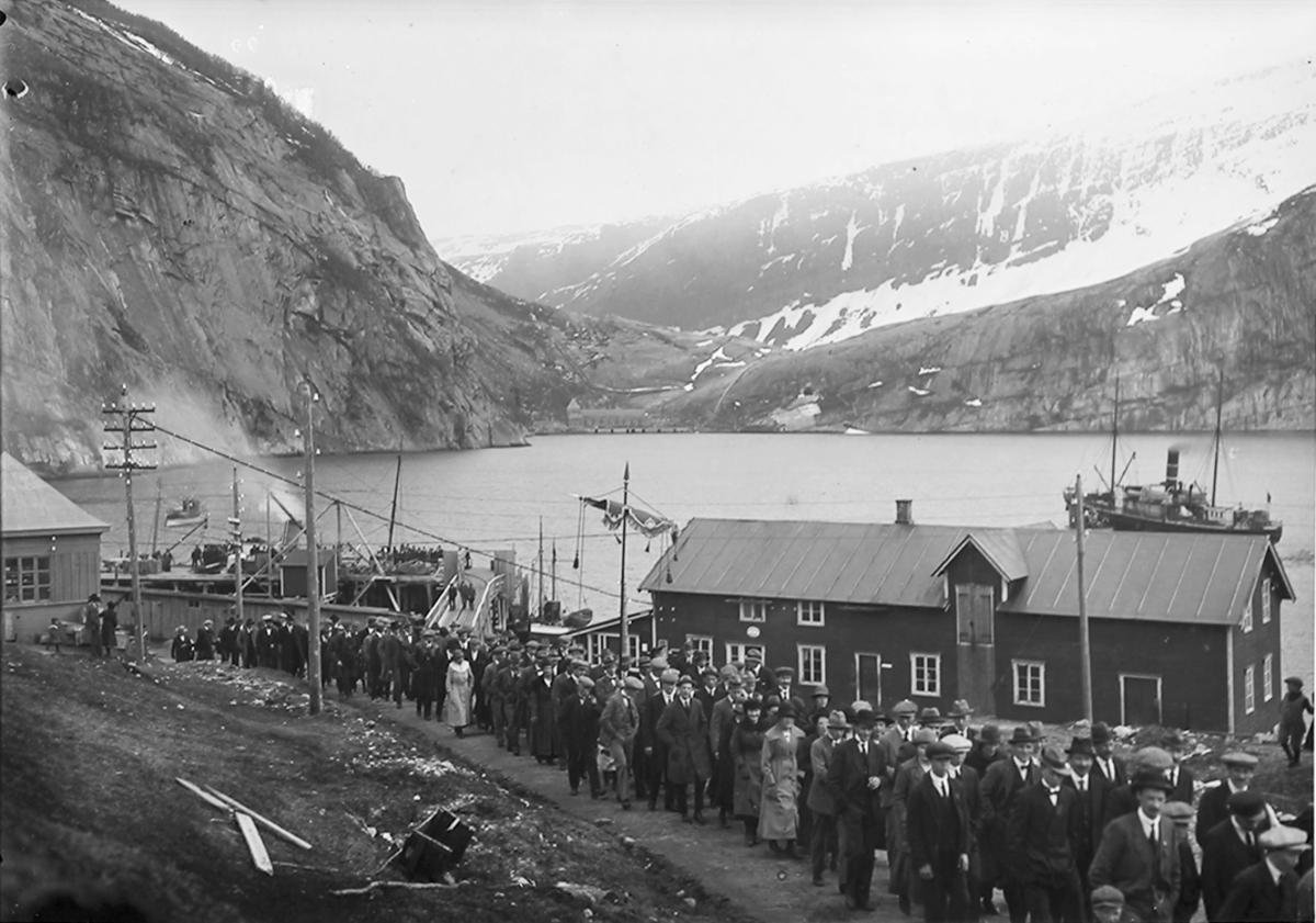 Glomfjord. Opptog. Barn med flagg, voksne. Kan være 17. mai eller 1. mai. Vei. Snø i veikanten.