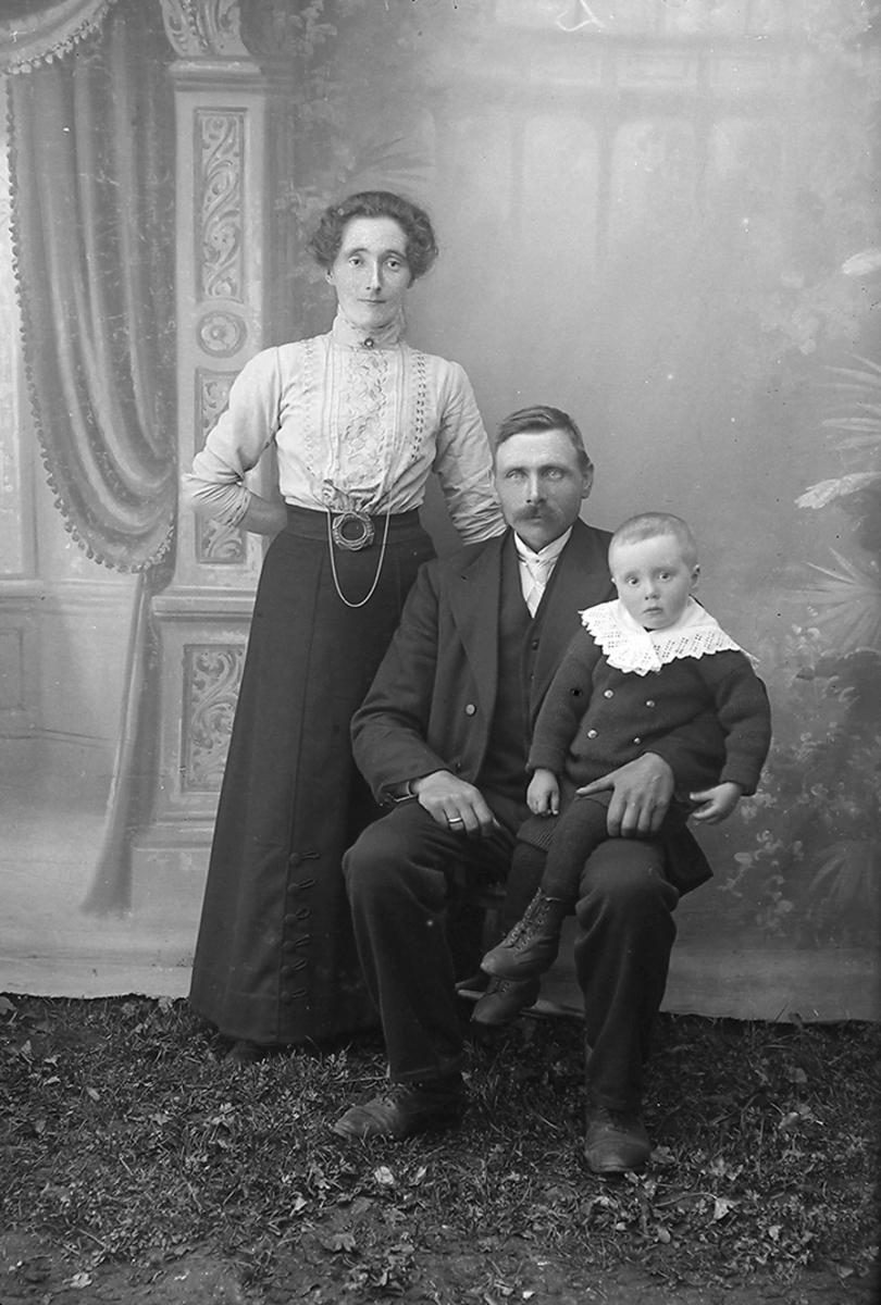 Familiebilde. Mor, far og en gutt. Faren sitter med gutten sittende på fanget, moren står ved siden av. Moren har på seg skjørt og bluse, faren har dress og gutten har en genser på seg.