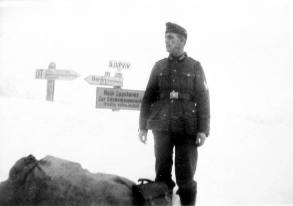 """Portrett. 1 person, mann i militæruniform. Utendørs ved """"veiskilt"""" - med bl.a. påskrift Berlin - Djupvik .."""