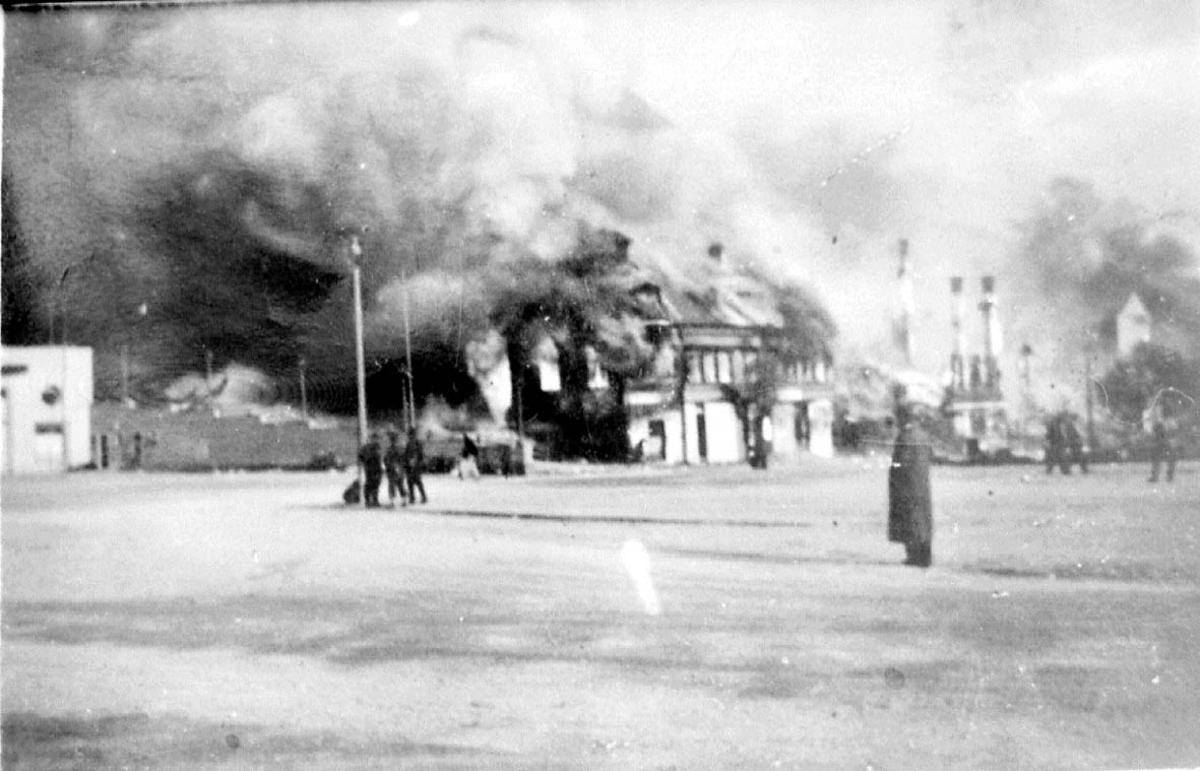 Tettsted - by i ruiner. Røyk stiger opp. Flere personer står og ser på.