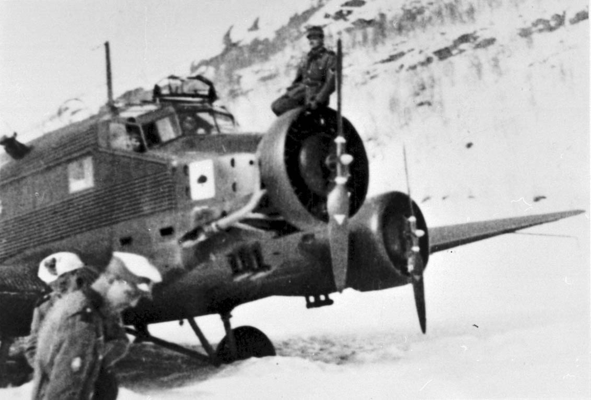 1 fly på bakken, Junkers Ju52. 2 personer, militært personell, ved flyet. Snø.