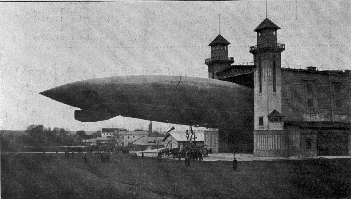 Utklipp: Ett luftskip, Korting-Wimpasseng (K-WI) millitær MIII, delvis inne i en luftskipshangar, (monteringshall).