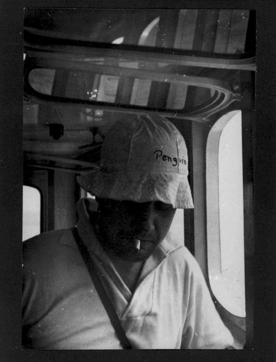 """Ombord i """"Polarbjørn"""". Fra styrehuset, en person, mann, med tropehatt."""