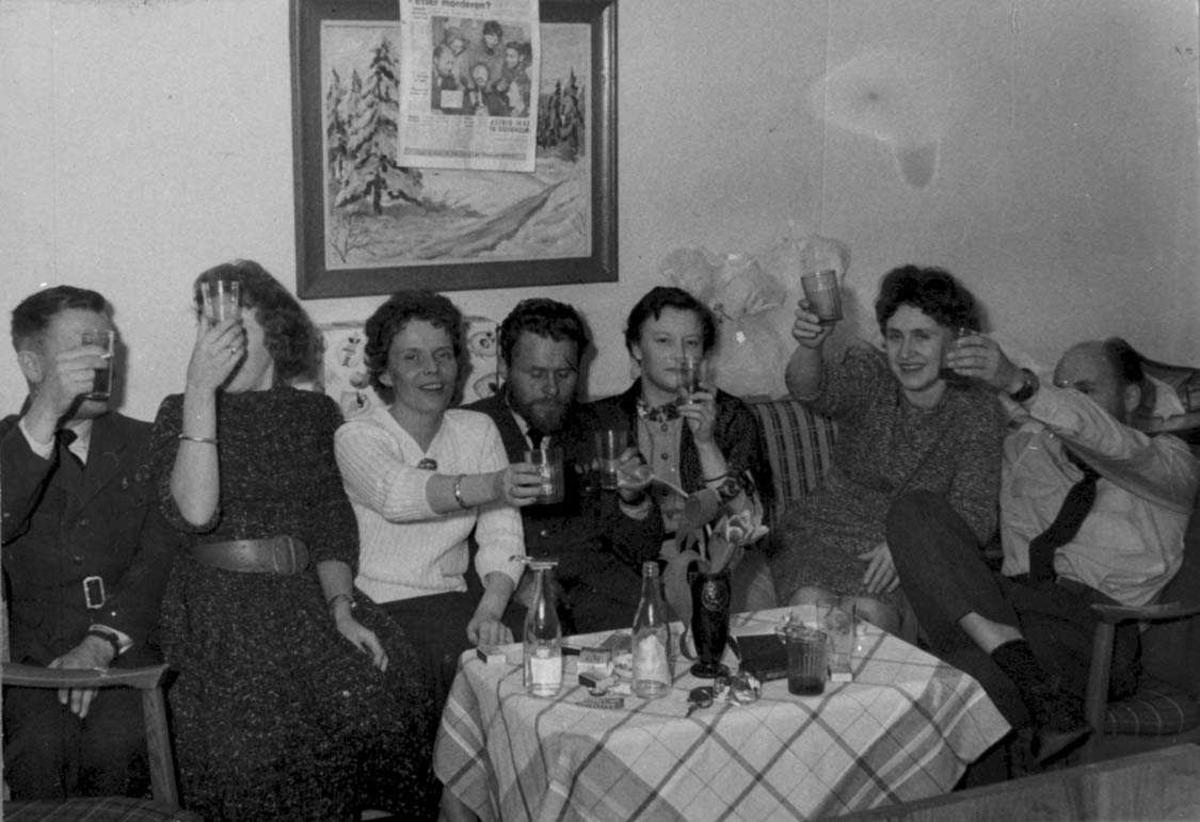 Flere personer, kvinner og menn, i festlig lag. Sitter rundt et lite bord.