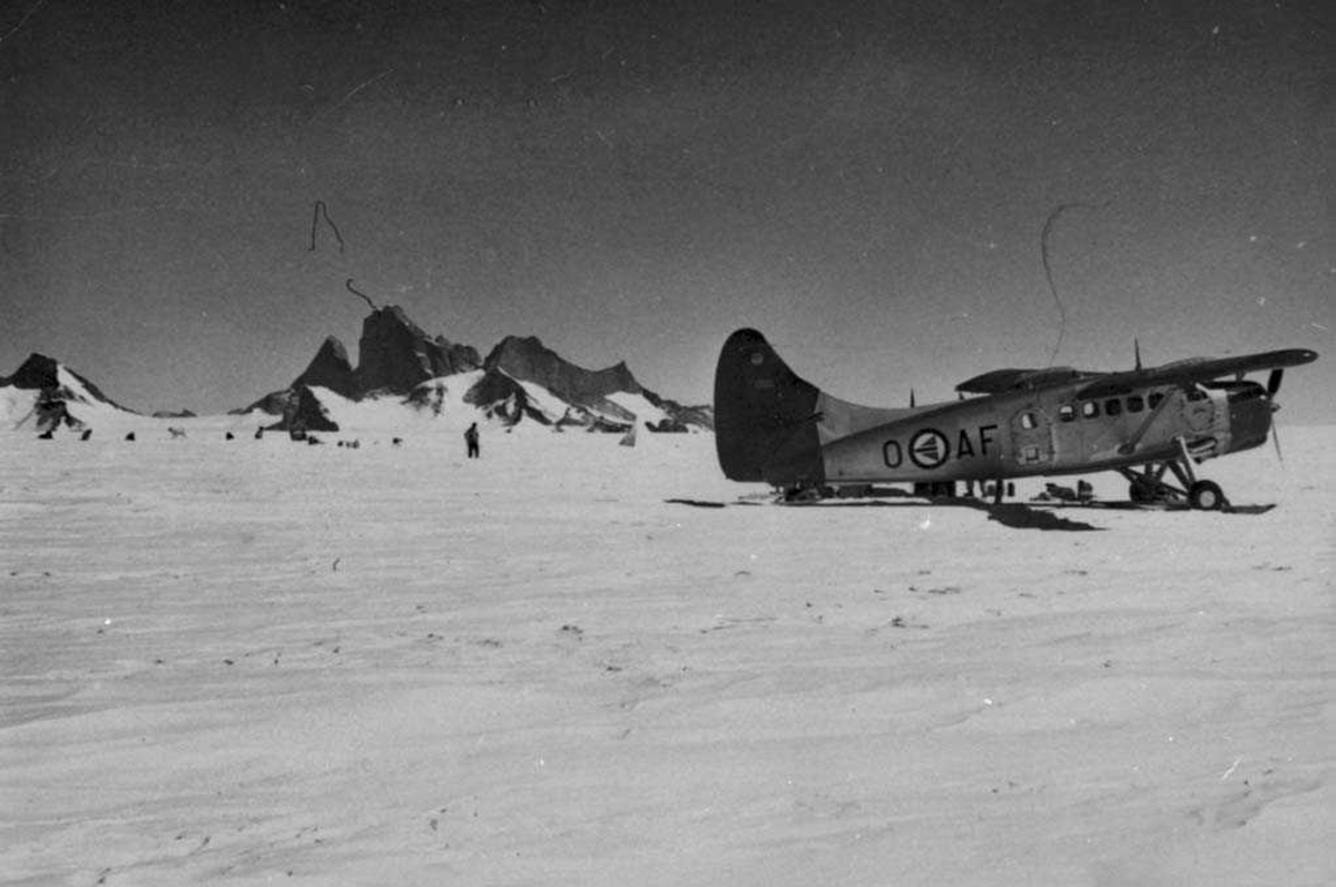 Ett fly med skiunderstell på bakken, Otter OAF. Noen personer og hunder i bakgrunnenb.