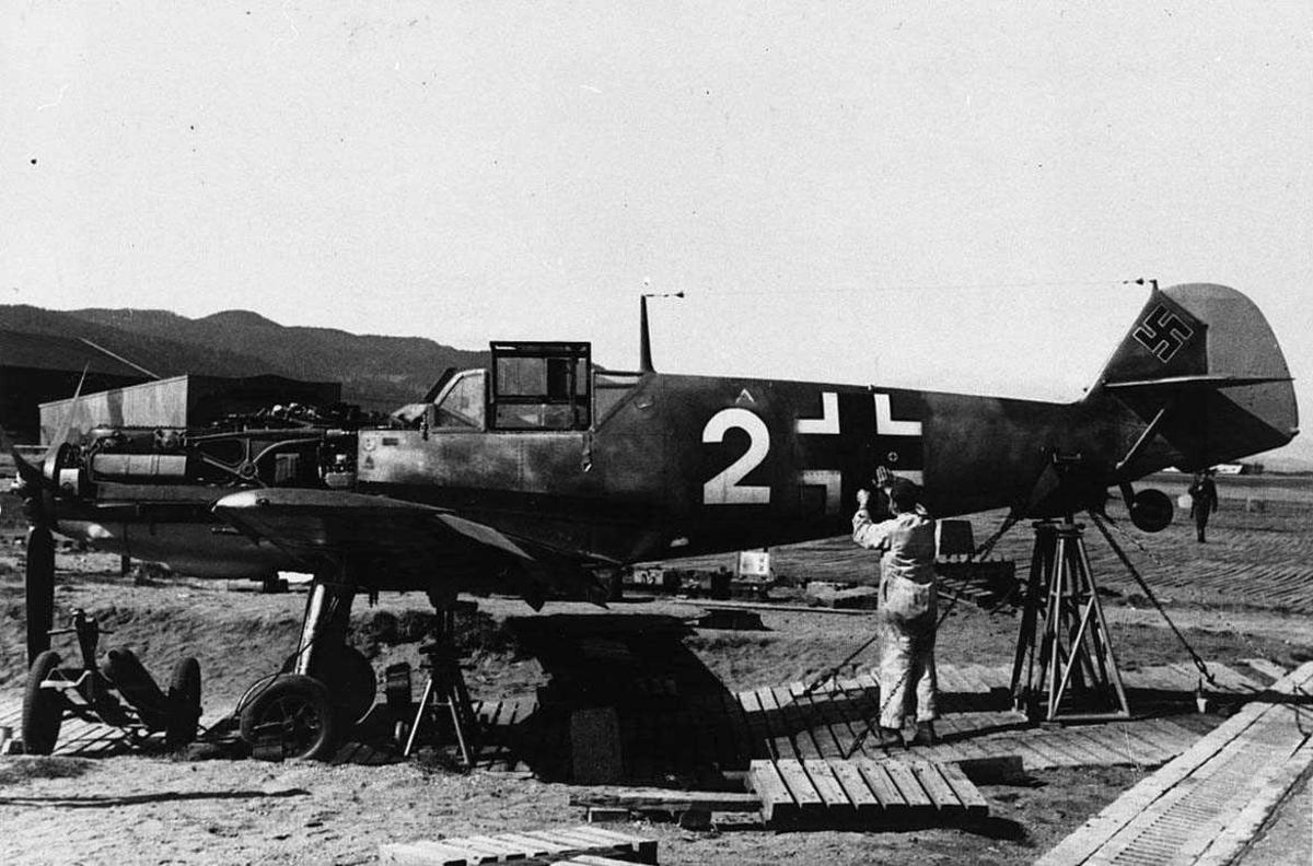 Lufthavn, tysk militert fly på bakken,  Bf109. Noen personer ved flyet.