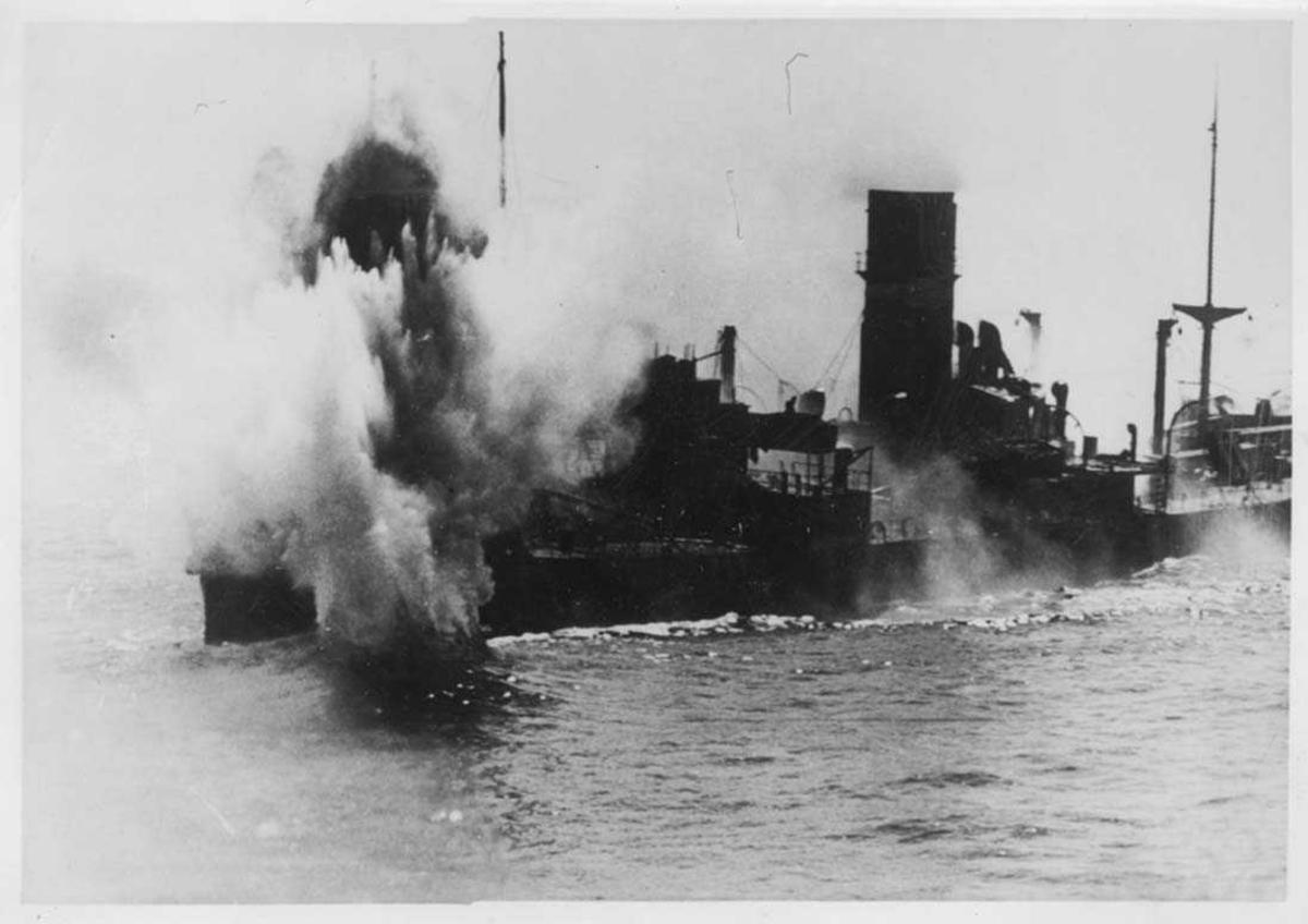 Et skip ute på havet som blir tuffet av et artilleri.