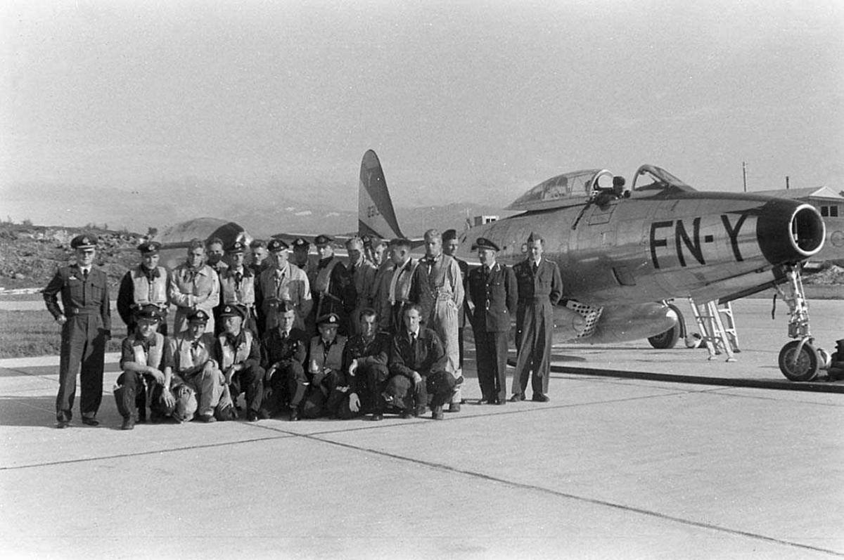 Gruppefoto av personell med jagerfly i bakgrunnen.
