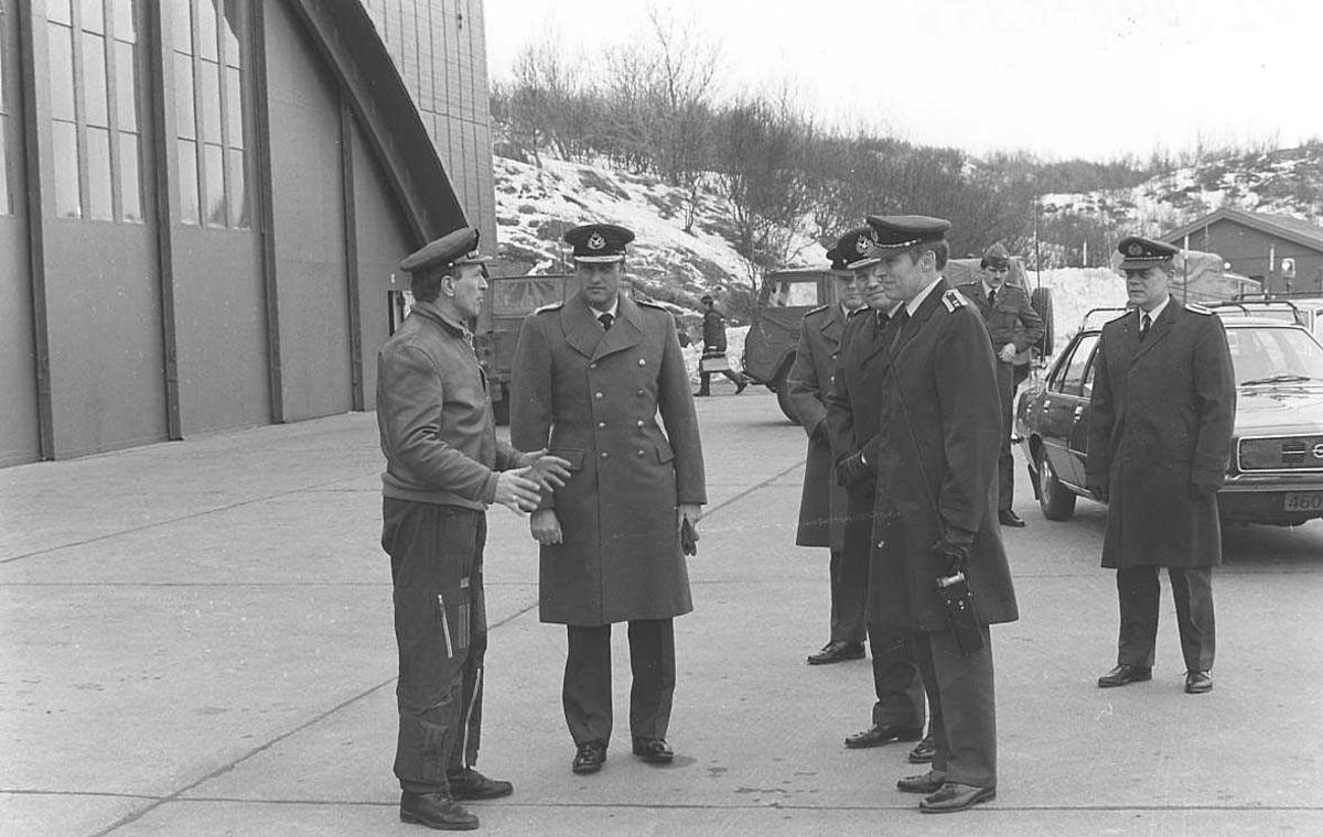 Personer samlet foran en hangar. Biler og en bygning i bakgrunnen.