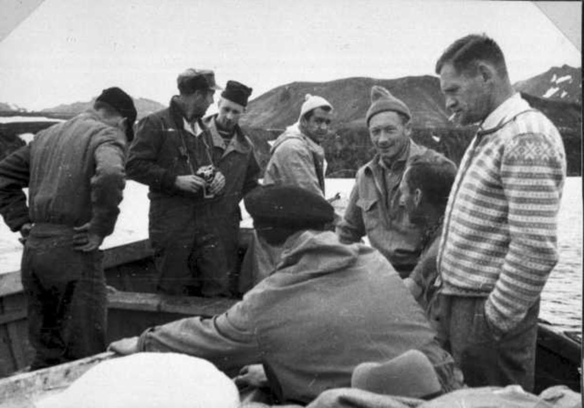Flere personer, menn, ombord i en åpen båt.