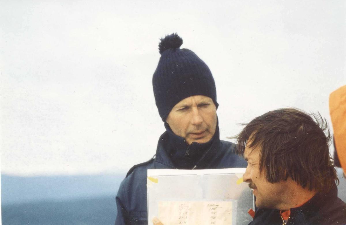 To personer, menn, studerer et ark med informasjon.