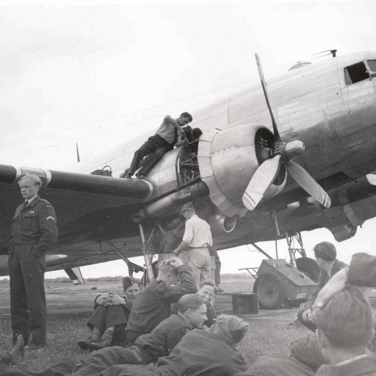 1 fly på bakken. DC3. 1 person som står og fikser den ene motoren. Flere personer på bakken ved flyet.