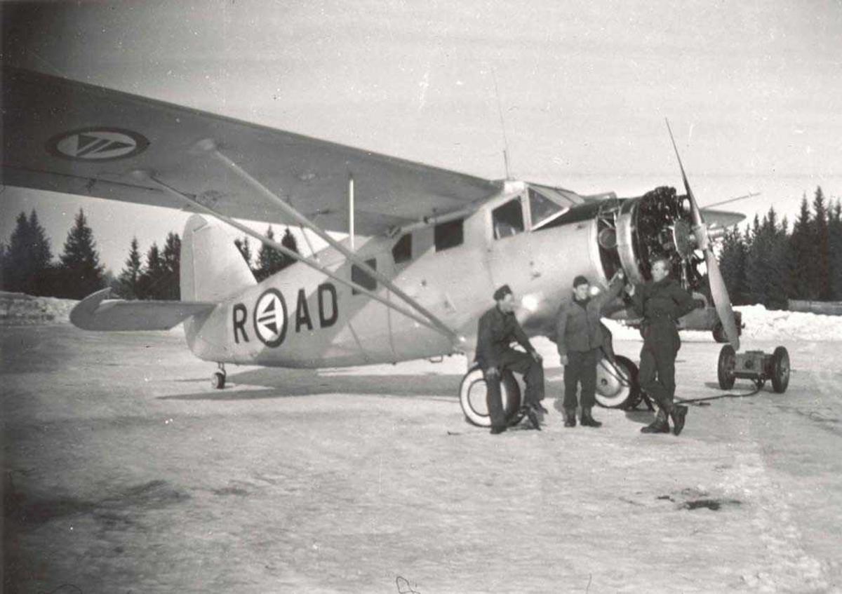 1 fly på bakken. Norseman. 3 personer står ved flyet. Personen til høyre er Knut Hafnor.