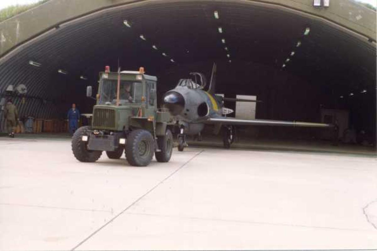 Lufthavn (flyplass). Ett fly på bakken, SAAB-32 Lansen, toseter som taues av traktor/kjøretøy inn i hangar.
