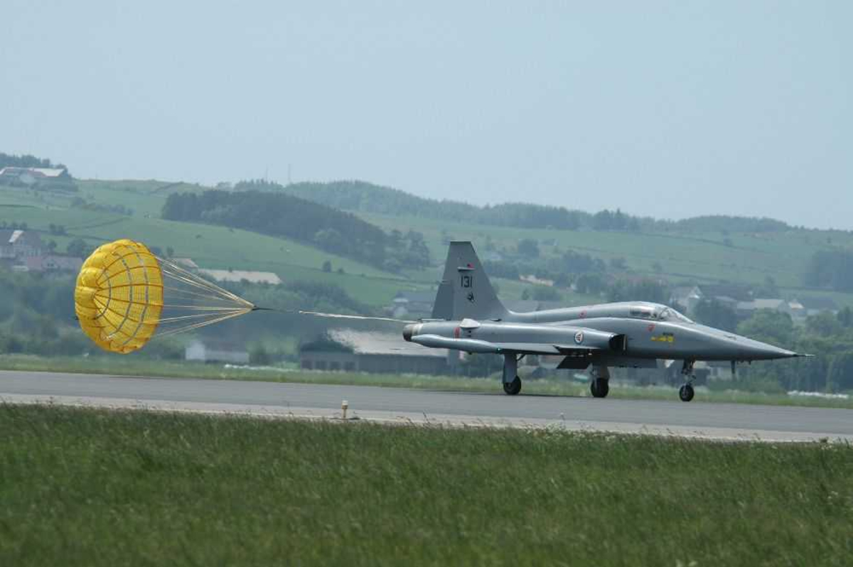 Lufthavn (flyplass). Ett fly på bakken Freedom Fighter 131 med åpen fallskjerm etter seg.