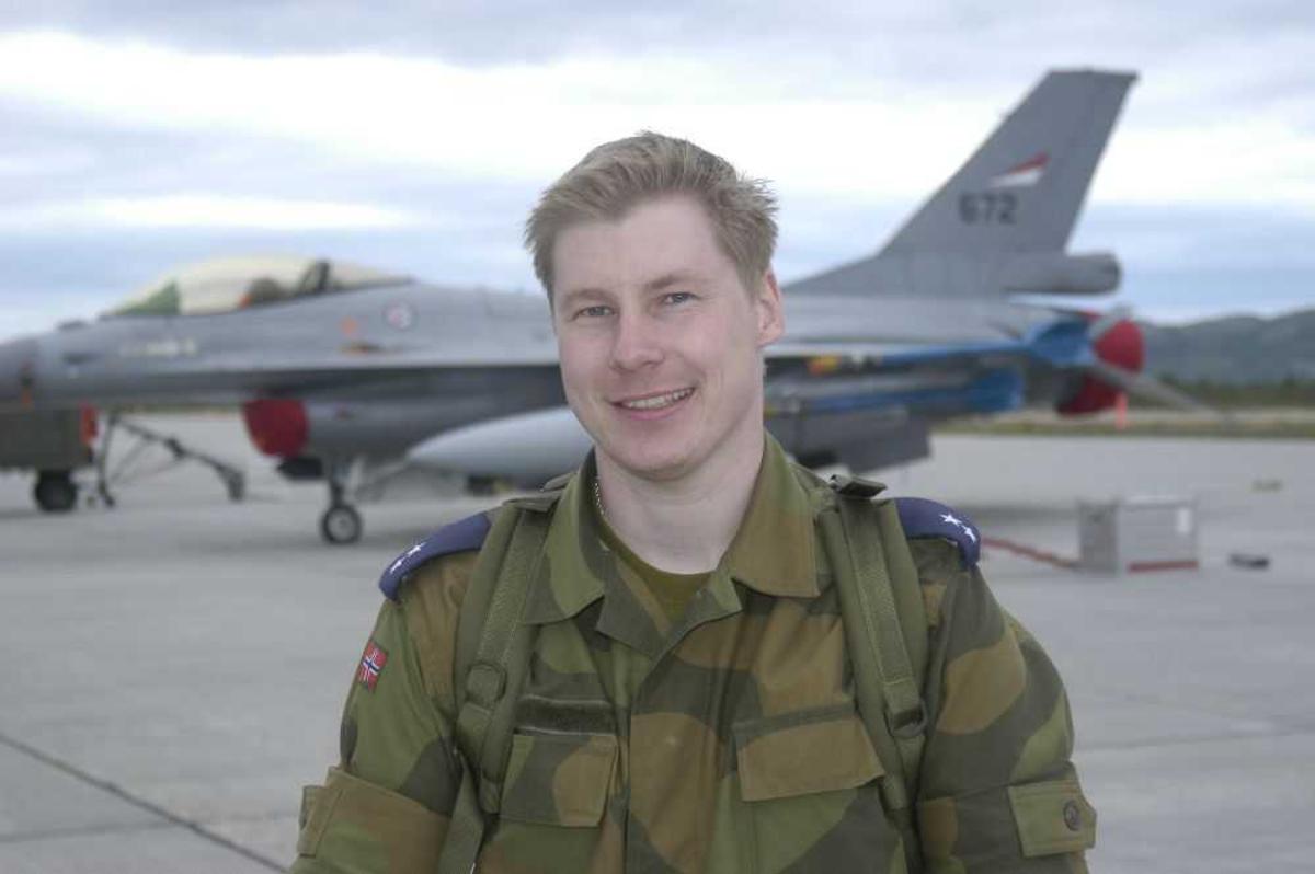 Lufthavn (flyplass). En person i militæruniform i forgrunnen. I bakgrunnen, F-16A Fighting Falcon, 672 fra RNoAF.