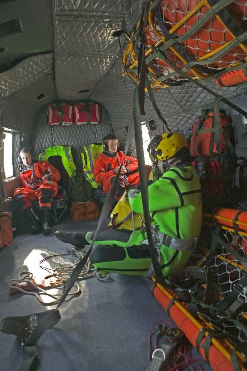 Tre personer og redbningsutstyr inne i flykabin.