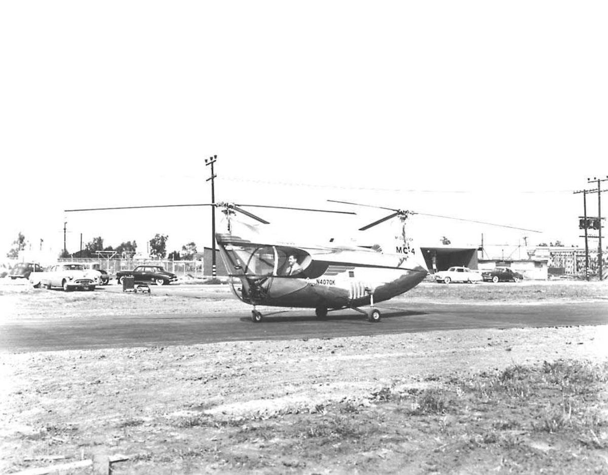 1 helikopter på bakken. McCulloch MC-4. 1 person inne i  cockpiten. Bygninger og biler i bakgrunnen.