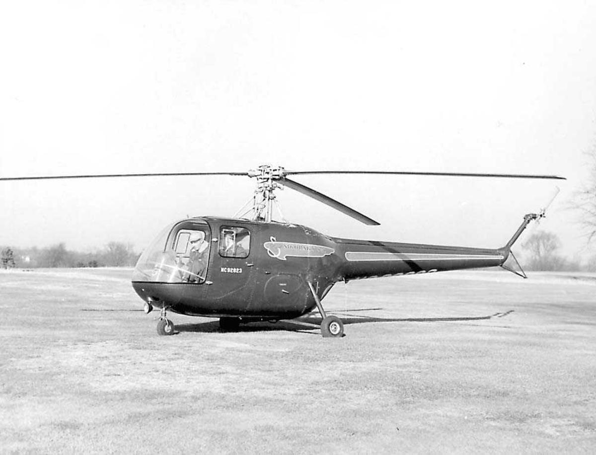 1 helikopter på bakken. Sikorsky S-52. 2 personer sitter i helikoptret.