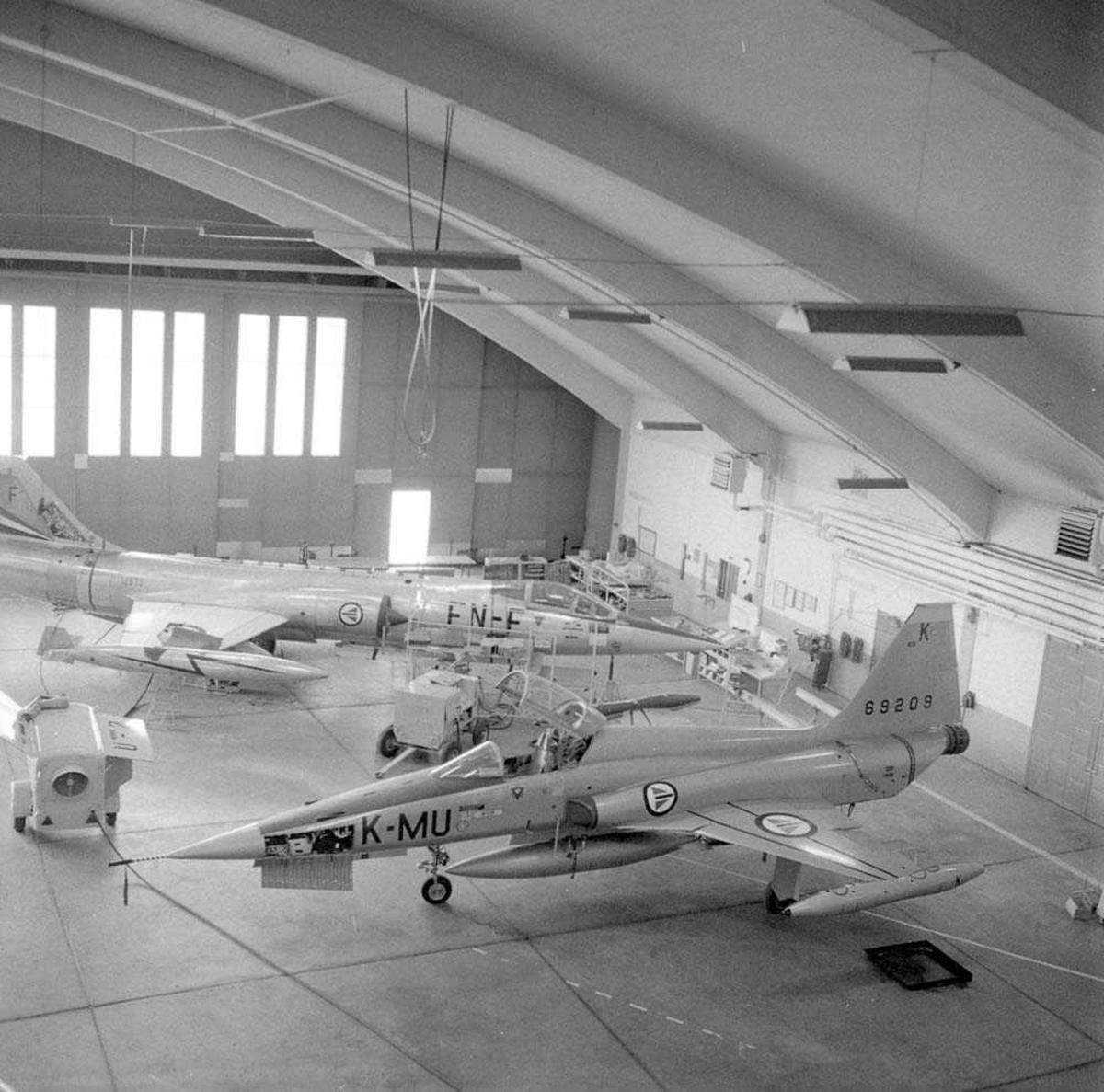 Her i Hangar A sees den første Freedomsfighter F-5-A som er til ettersyn på Bodø flystasjon. Jagerflyet har kjennetegn MU-K og serie nr. 69209. I bakgrunnen sees en  F-104-G Starfighter med kjennetegn FN-F og serie nr. 12630.
