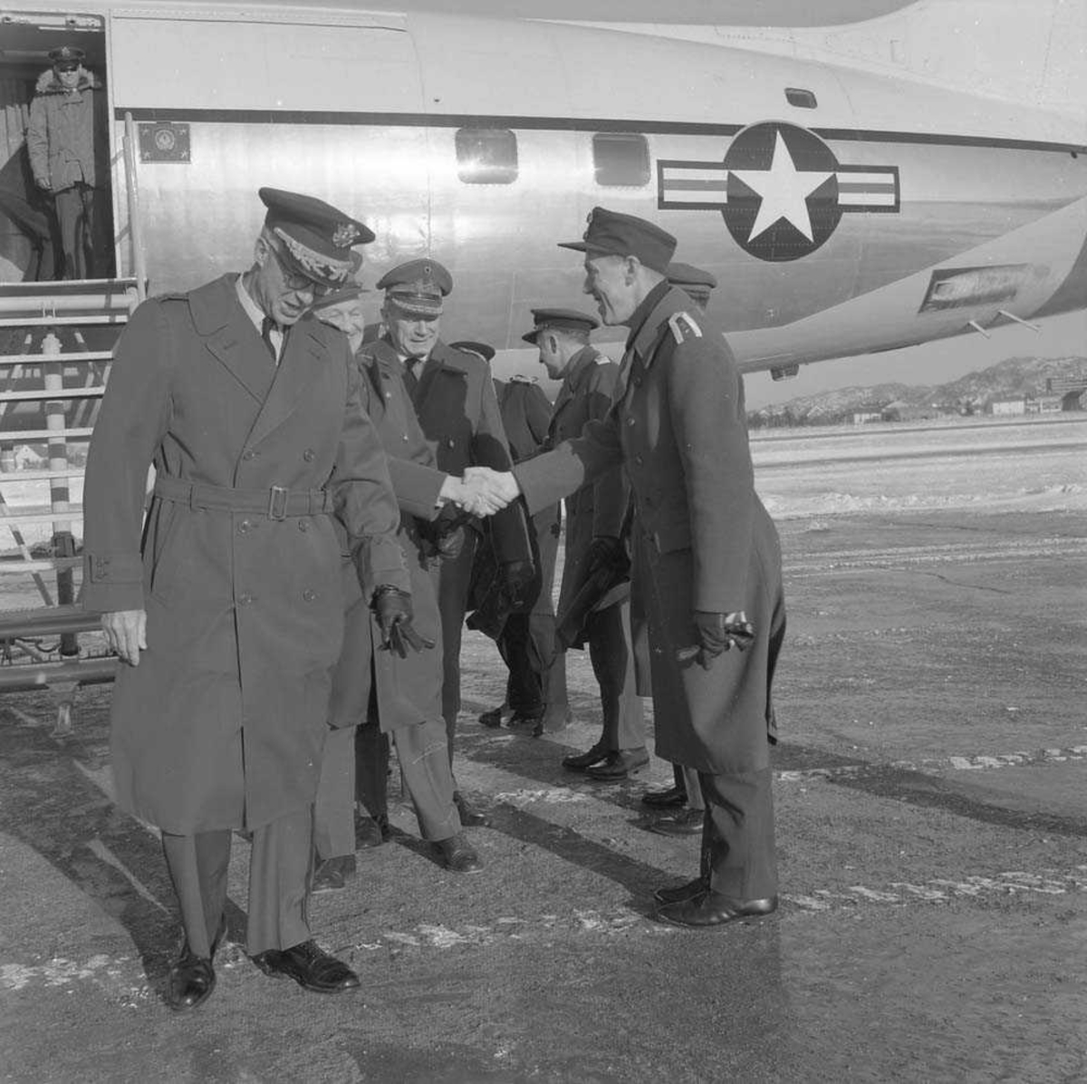 General Goodpasler besøker Bodø flystasjon. Han sees til venstre i bildet og til høyre sees Oberst E. Tjensvoll, som mottar besøket. Flyet i bakgrunnen er en Douglas DC-6.
