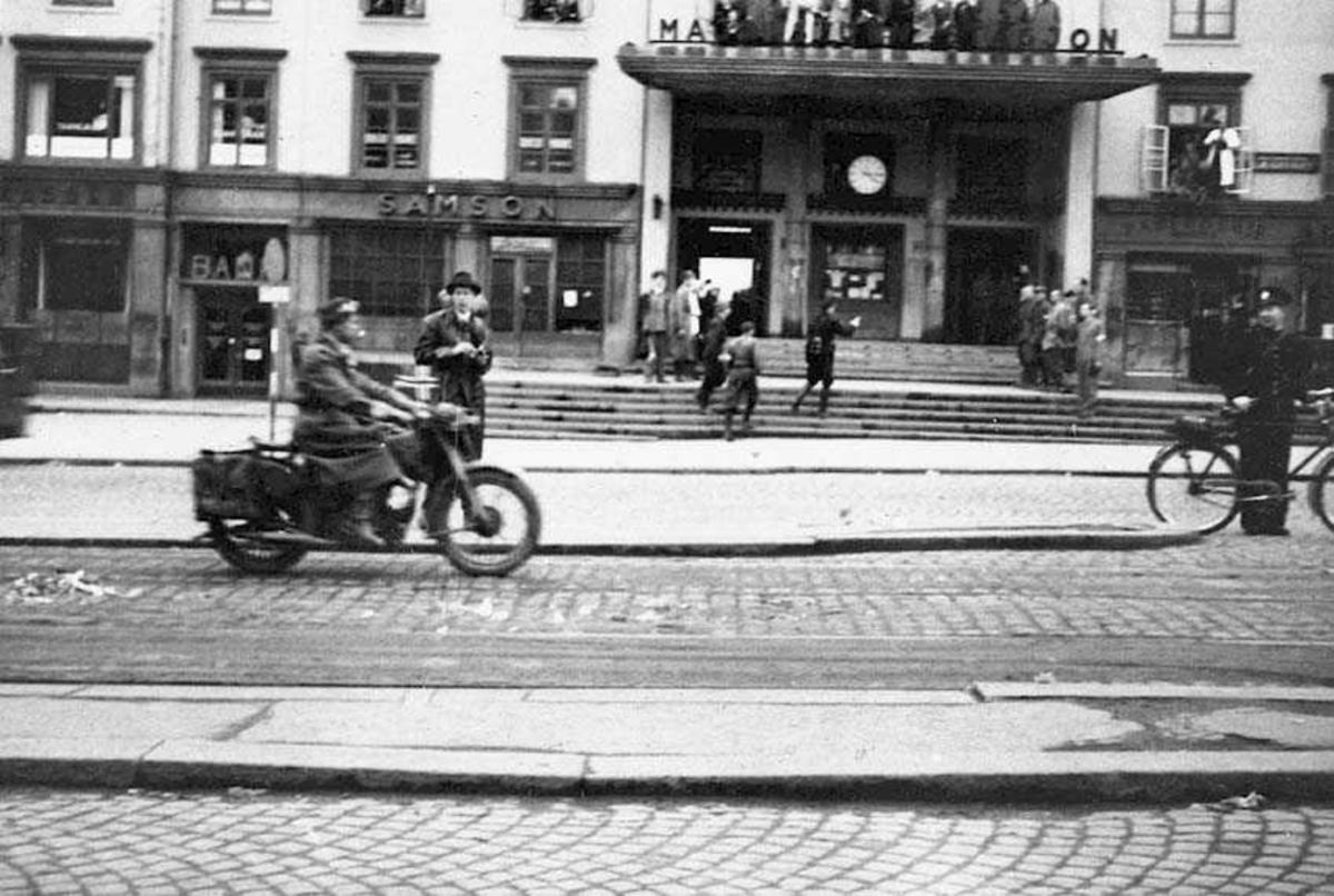Flere personer på en plass. En kjører på en motorsykkel og en står med en sykkel. Bygning i bakgrunnen.
