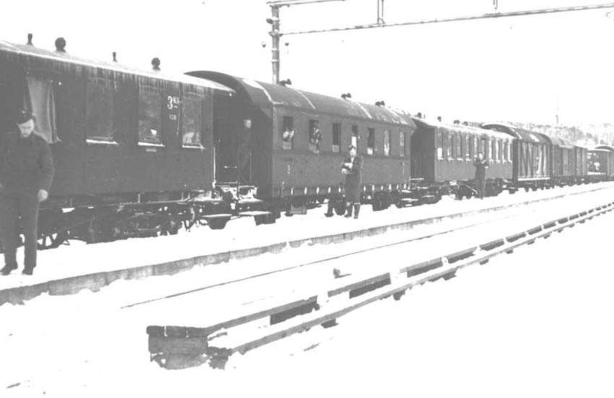 Jernbanevogner. Tre passasjervogner fremst med godsvogner bak. Tre personer står foran vognene.