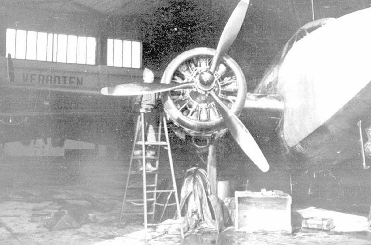 Et fly som står i en hangar. En person som står på en gardintrapp ved propellen.