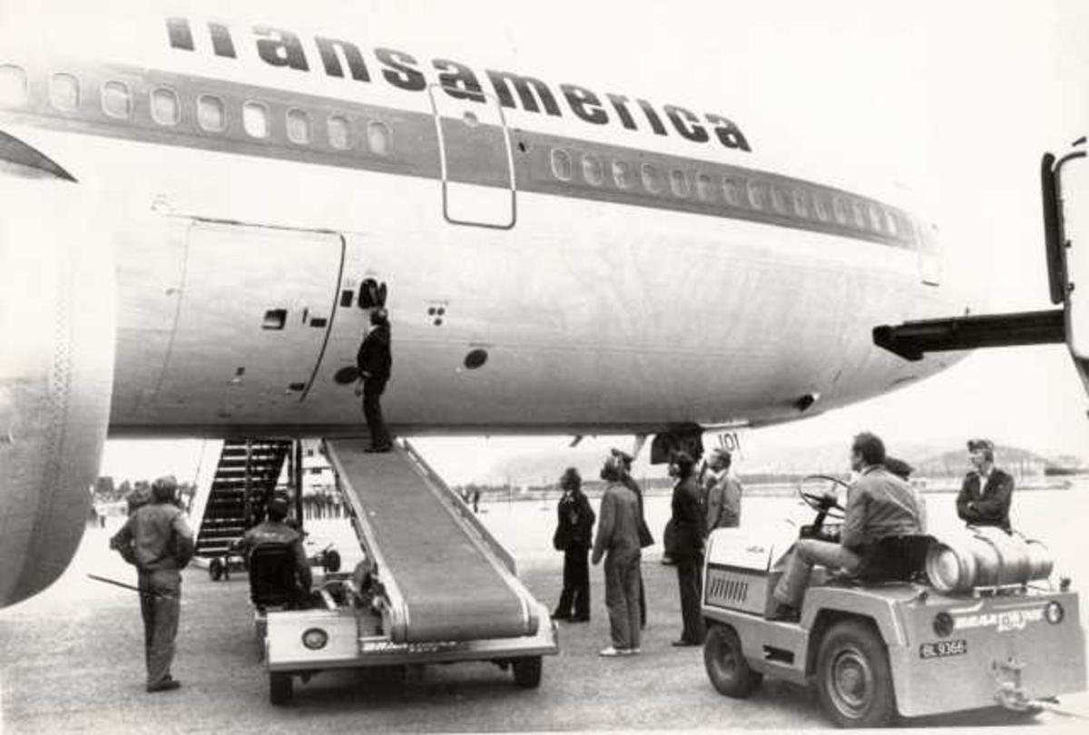 Ett fly på bakken. McDonnell Dounglas DC-10. Flere personer ved flyet.