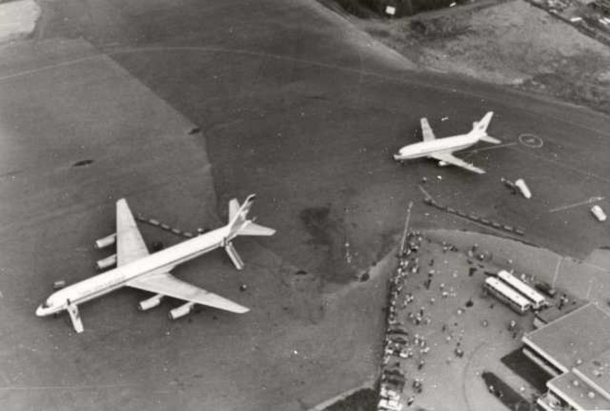 To fly på bakken. Douglas DC-8 og Boeing 737-200. Flere mennesker ved terminal.