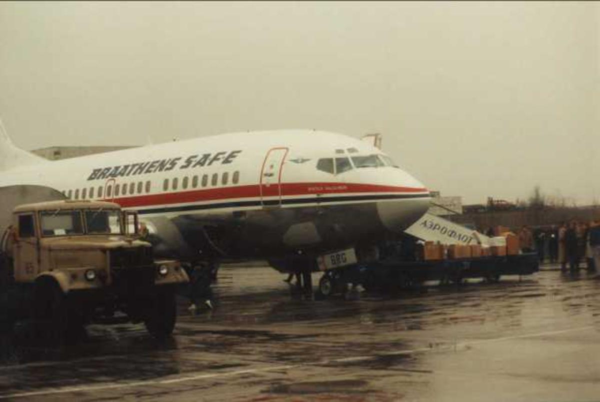 Flere fly på bakken. Ett Boeing 737-405 LN-BRG. Flere personer ved flyet.