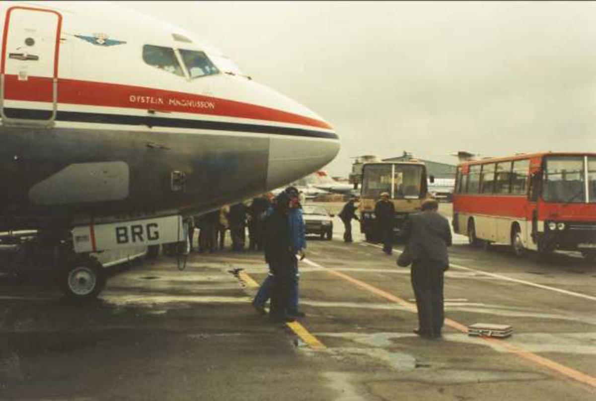 Ett fly på bakken. Boeing 737-405 LN-BRG. Flere personer ved flyet.