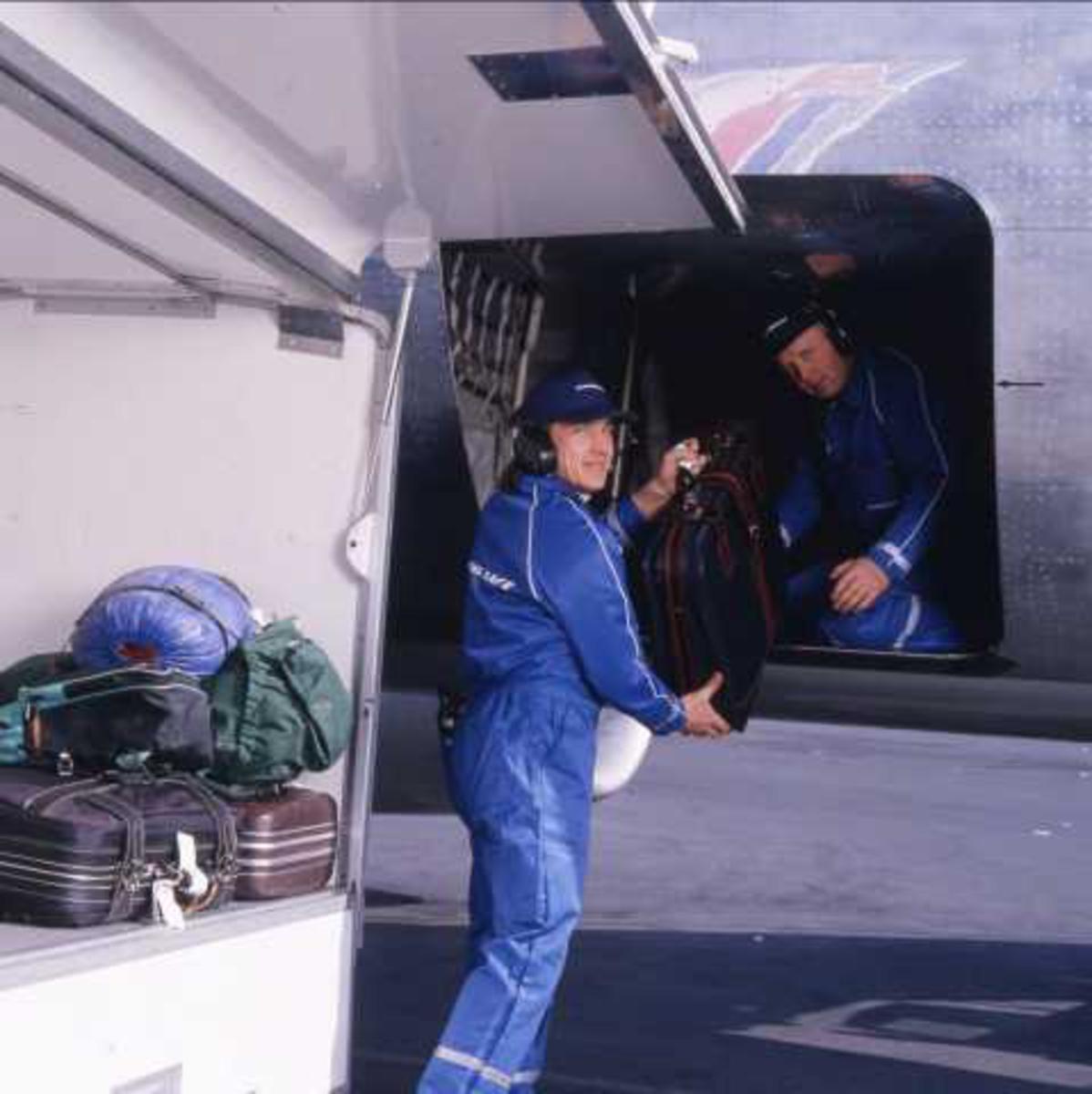 Ett fly på bakken. To personer, en inne i lasterom, en utenfor. Bagasje.