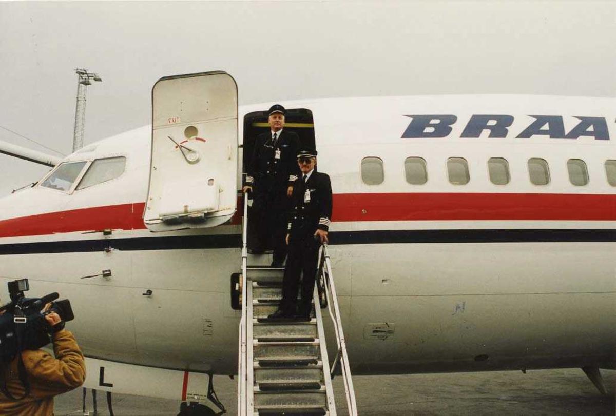 "Ett fly på bakken. Boeing 737-296 "". Tre personer. To personer i flytrapp, kapteiner, en kameramann nede til venstre."