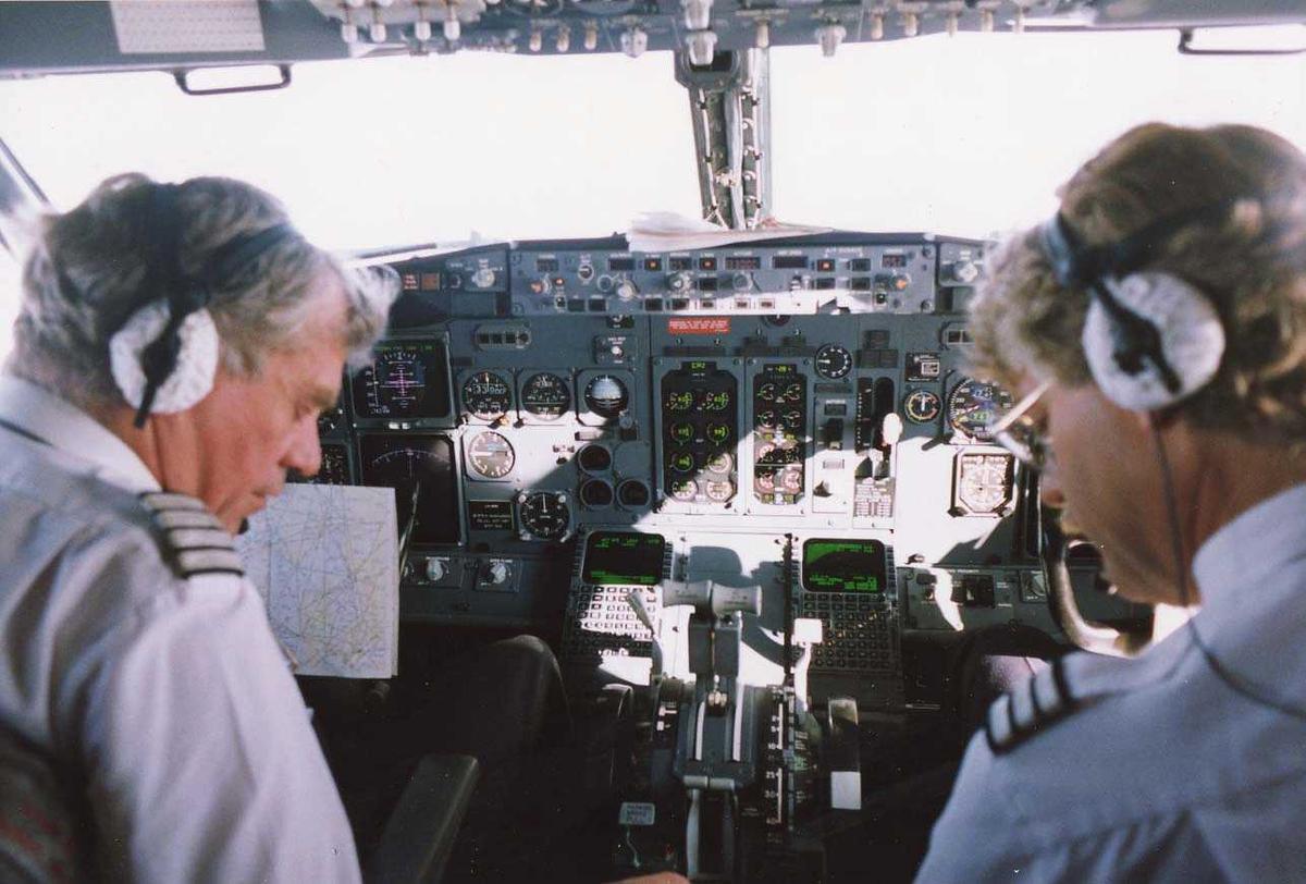 """Ett fly i luften. Boeing 737-505 LN-BRG """"Øystein Magnusson"""". To personer i cockpit, kaptein og styrmann."""