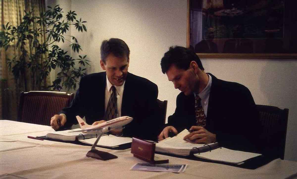 To personer sittende bak bord. Per G. Braathen til høyre. Signering av paprirer.