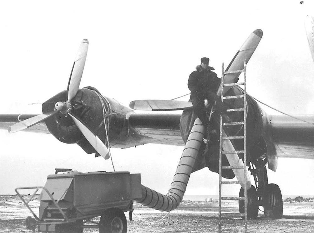 En person som sitter på propellen til en Douglas DC-4 Skymaster. En oppvarmingsmaskin er koblet til en av motorene med en slange. Begge inntakene til motorene er tildekket.