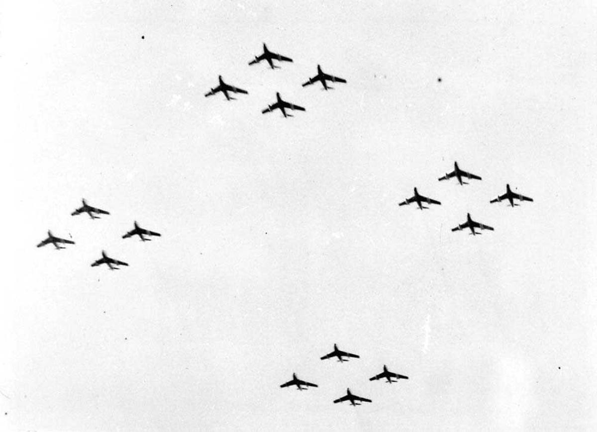 Luftfoto. 16 fly i formasjon i fire grupper på fire. F-86F Sabre.