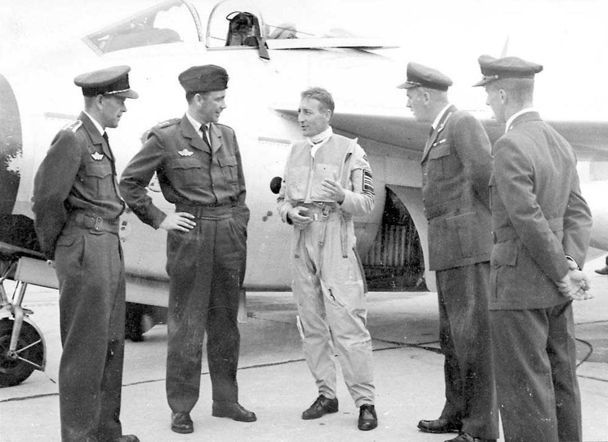 Fem personer som står foran et fly.  Fire i militæruniform og en i flydrakt.