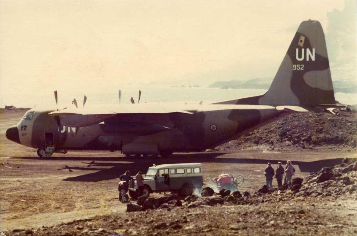 Ett fly på bakken, Hercules. Flere personer og et kjøretøy i forgrunnen.