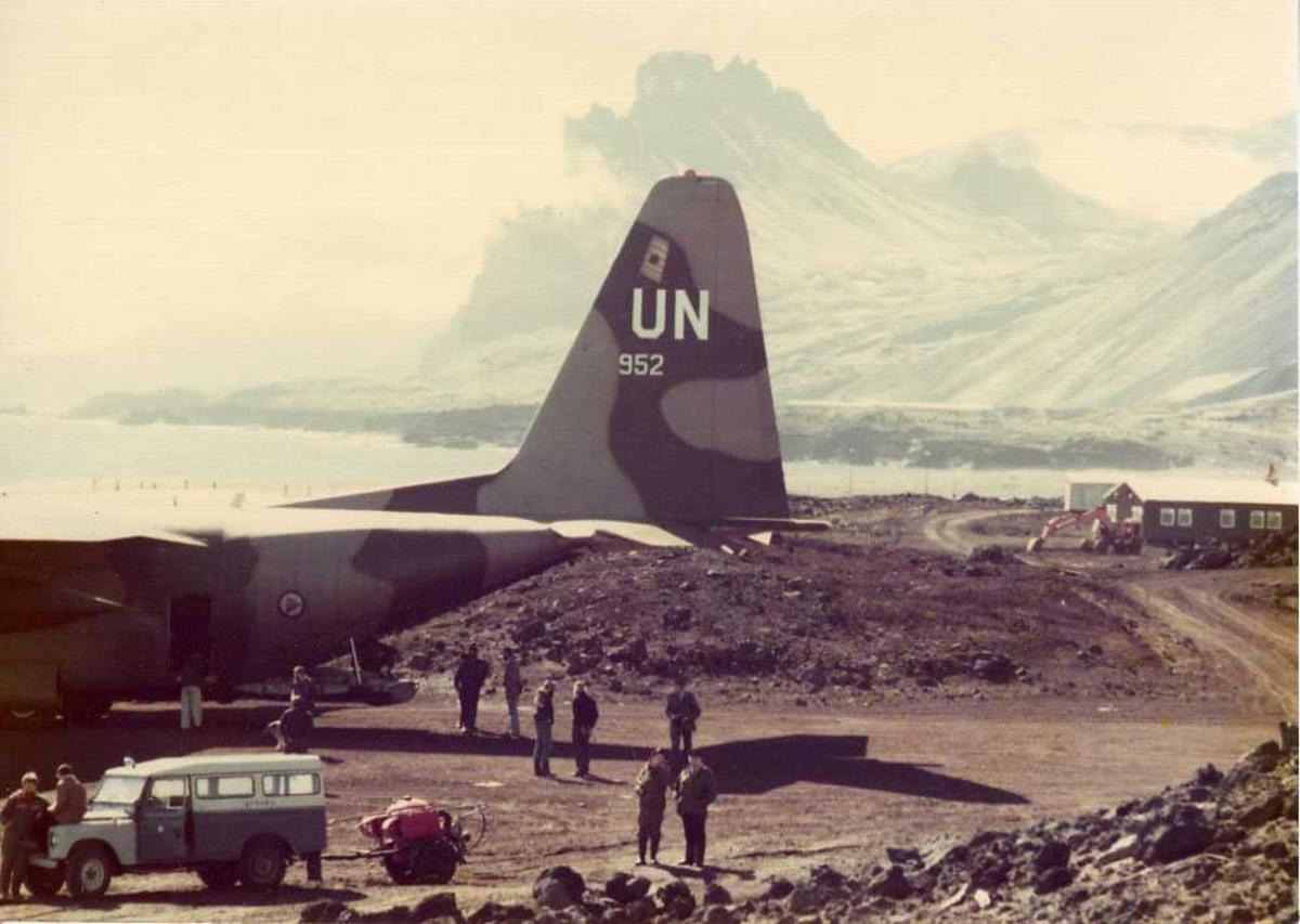 Flere personer ved et fly på bakken, Hercules. Arbeidsbrakke og fjell i bakgrunnen.