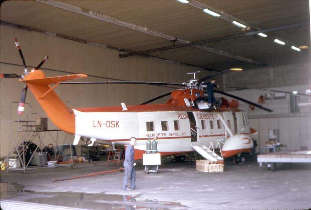 Ett helikopter inne i en hangar. Sikorsky S-61N Mk II, LN-OSK fra Helikopter Service. En person står foran helikoptret.