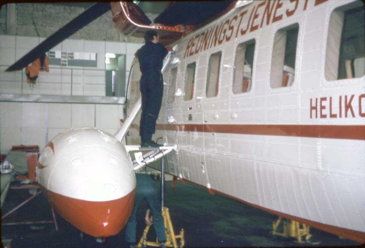 En person som arbeider på et helikopter inne i en hangar. Sikorsky S-61N Mk II, LN-OSK fra Helikoter Service.