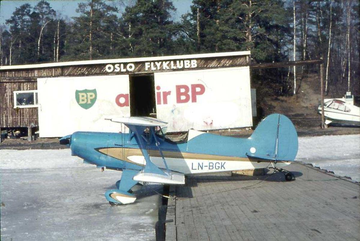 Ett fly som står med forparten på et isete vann og bakparten på ei trekai., EAA Acro Sport, LN-BGK. Bygning og et fly i bakgrunnen.