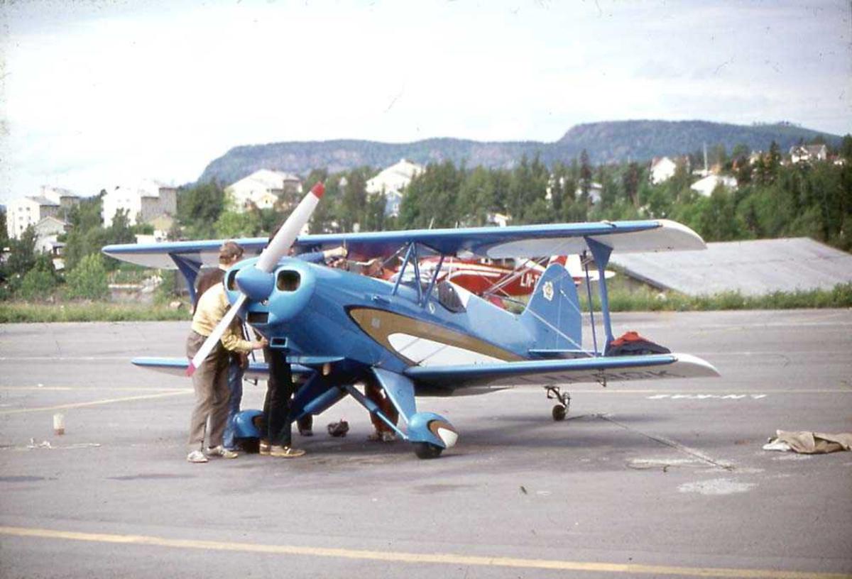 Lufthavn. Ett fly på bakken, EAA Acro Sport. Flere personer ved flyet. Et fly, bygninger og fjell i bakgrunnen.