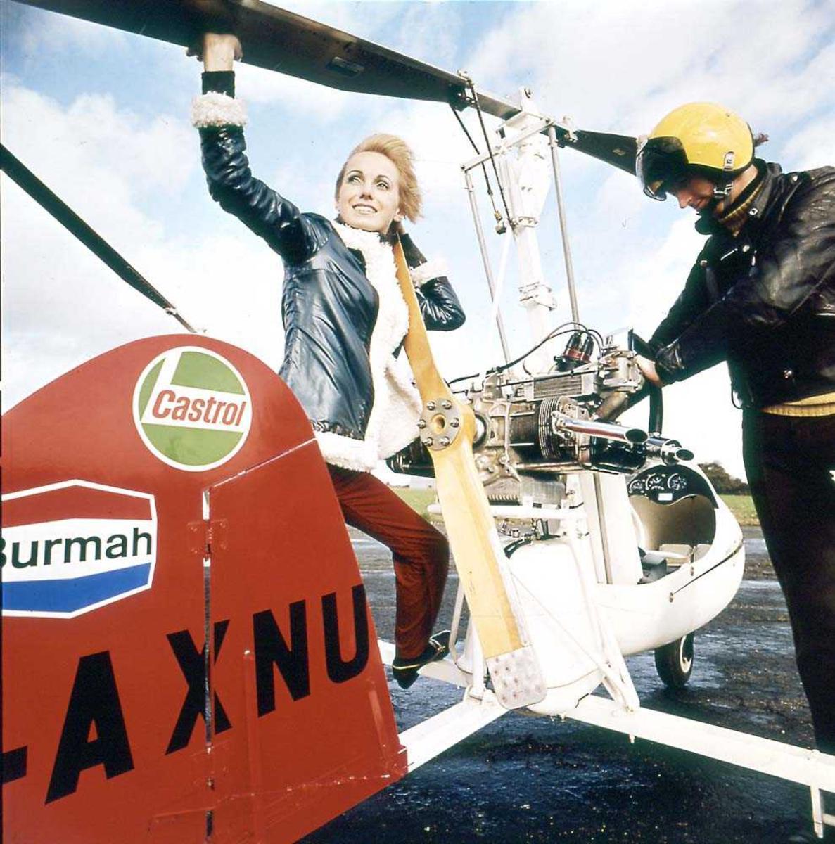 Ett helikopter på bakken, Campbell Cricket Autogyro. To personer ved helikoptret.