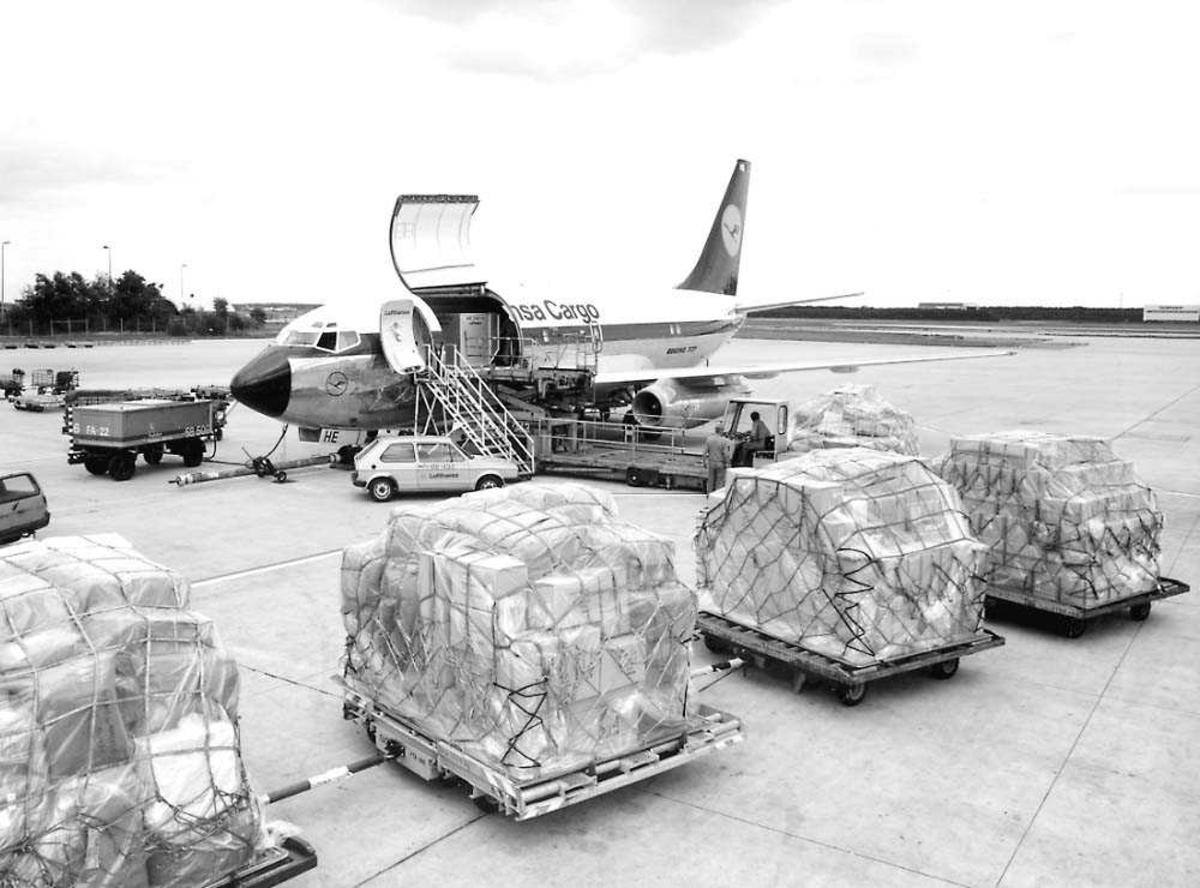 Lufthavn. Ett fly på bakken Boeing 737-200F (fraktfly) D-ABHE fra Lufthansa Cargo. Flere paller med last foran flyet.