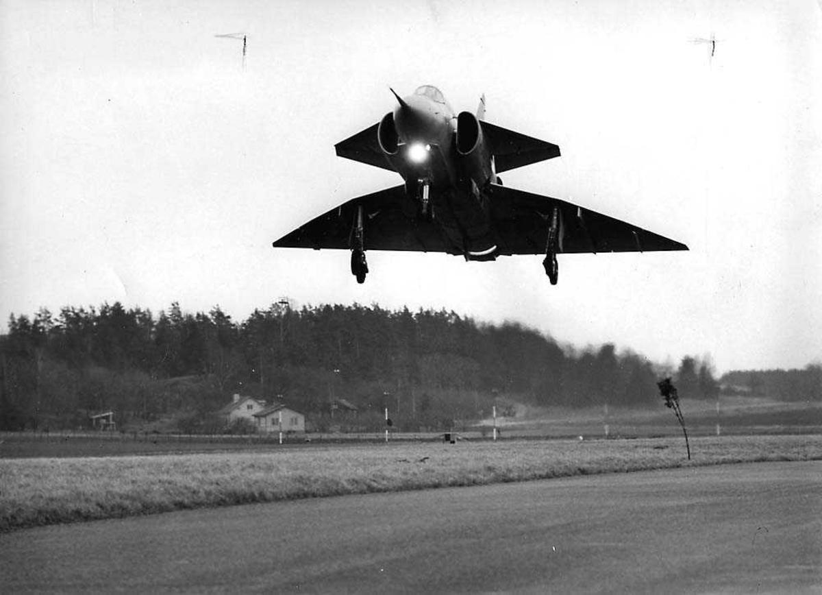 Ett fly i luften like over bakken, Saab J37 Viggen. Bygninger og skog i bakgrunnen.