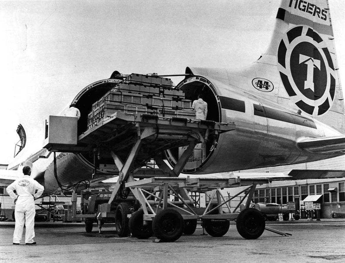 Lufthavn. Ett fly på bakken med åpent haleparti og en palle frakt i åpningen, Canadair CL-44 transport fra Flying Tiger Line. Bygninger i bakgrunnen.